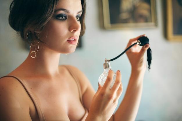 Attractive seductive sensual stylish woman in boho dress sitting vintage retro cafe holding perfume Free Photo