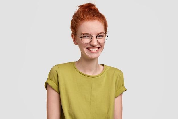 Attraente donna sensuale ridacchia, ride di una storia divertente, ha i capelli rossi pettinati a crocchia, indossa occhiali da vista, modelle contro il muro bianco, sembra amichevole e spensierata. concetto di felicità Foto Gratuite