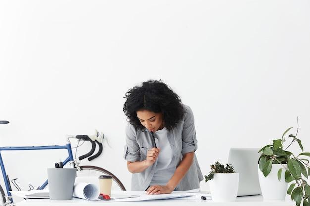 Привлекательная серьезная и целеустремленная молодая женщина-инженер смешанной расы с вьющимися волосами, держащая ручку Бесплатные Фотографии
