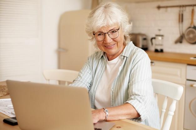 魅力的な真面目な自営業の女性年金受給者は、自宅から遠く離れて働いて、開いたポータブルコンピューターの前のキッチンに座って、眼鏡をかけています。人、年齢、仕事、職業の概念 無料写真