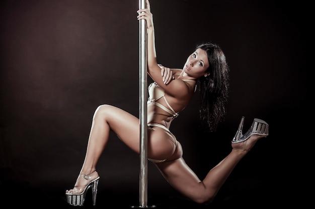 Ballerino del palo della donna sexy attraente che esegue contro il fondo grigio Foto Gratuite