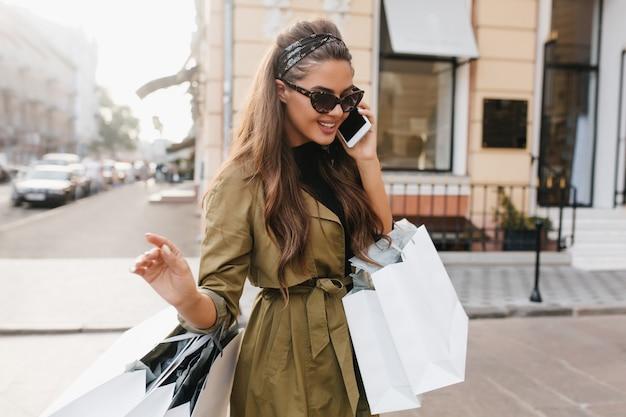 Attraente donna shopaholic con pelle abbronzata, parlando al telefono con un sorriso carino Foto Gratuite