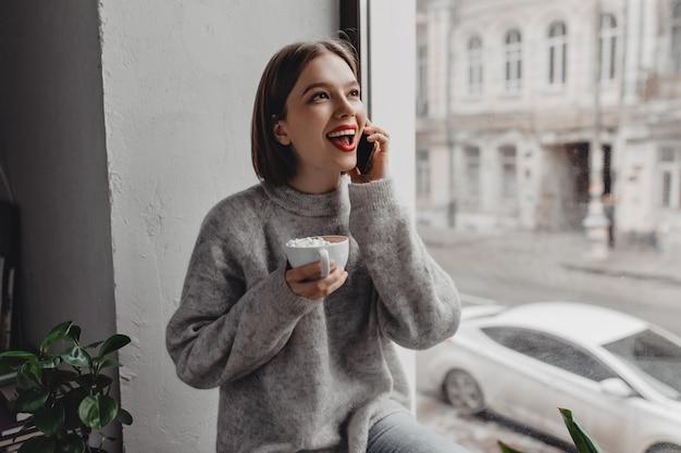 電話で話し、窓にマシュマロとココアのカップを保持している灰色のセーターに身を包んだ赤い口紅を持つ魅力的な短い髪の少女。 無料写真