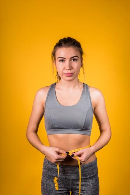 Attractive slim lady measuring waist Free Photo