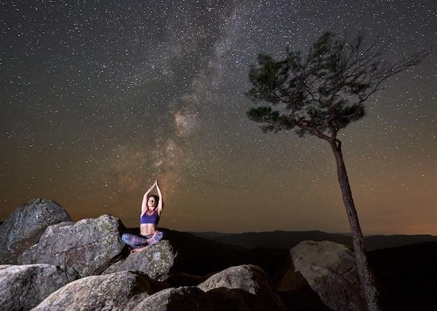 ヨガをしているロータスの姿勢で巨大な岩の上に一人で座っている魅力的なスリムな観光女の子 Premium写真