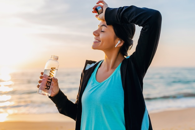 Attractive slim woman doing sport exercises on morning sunrise beach in sports wear, thirsty drinking water in bottle, healthy lifestyle, listening to music on wireless earphones, smiling happy Free Photo