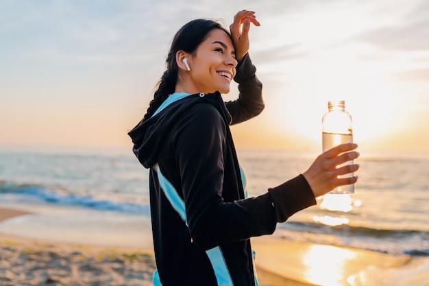 Привлекательная стройная женщина делает спортивные упражнения на утреннем пляже восхода солнца в спортивной одежде, пить питьевую воду в бутылке, здоровый образ жизни, слушает музыку на беспроводных наушниках, чувствуя себя горячим Бесплатные Фотографии