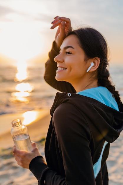 Привлекательная стройная женщина делает спортивные упражнения на утреннем пляже восхода солнца в спортивной одежде, пить питьевую воду в бутылке, здоровый образ жизни, слушает музыку на беспроводных наушниках, жаркий летний день Бесплатные Фотографии