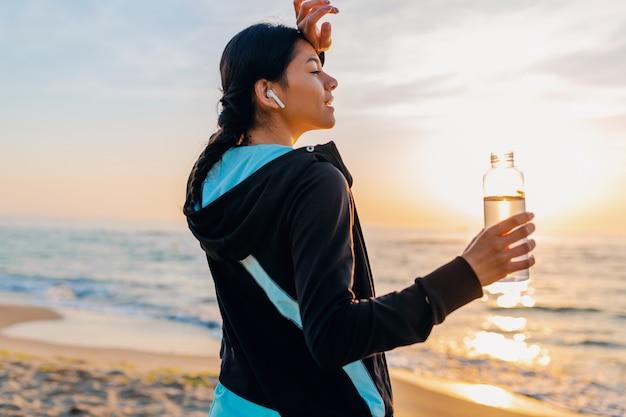 Привлекательная стройная женщина делает спортивные упражнения на утреннем пляже восхода солнца в спортивной одежде, пить питьевую воду в бутылке, здоровый образ жизни, слушает музыку на беспроводных наушниках, улыбается счастливым Бесплатные Фотографии