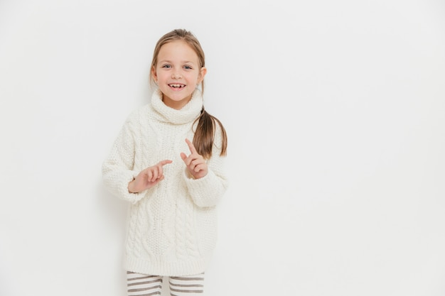 Attractive small female child in warm winter sweater, hears positive story from friend, stands against white Premium Photo