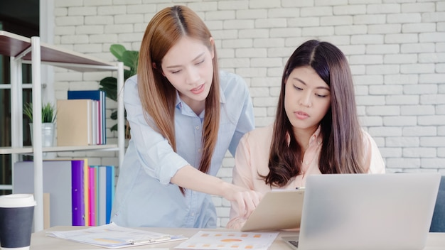 Attractive smart creative asian business women in smart casual wear working on laptop while sitting Free Photo