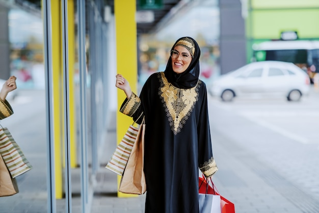 Attractive smiling arab woman in traditional wear looking at shop window while standing with shopping bags in hands. Premium Photo