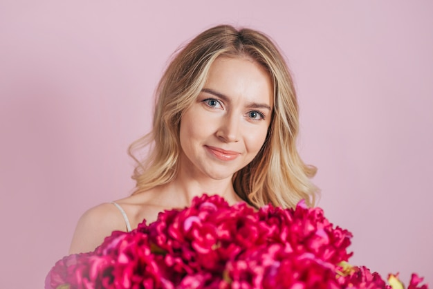 An attractive smiling blonde young woman with red flower bouquet against pink background Free Photo