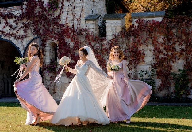 Attractive smiling bride and bridesmaids are dancing and having fun in front of stone building covered with red ivy Free Photo