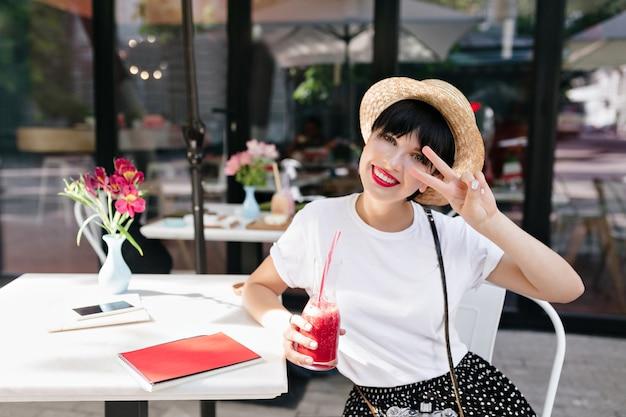 夏の日においしいレモネードを飲みながら喜んでポーズをとる淡い肌の魅力的な笑顔の女の子 無料写真