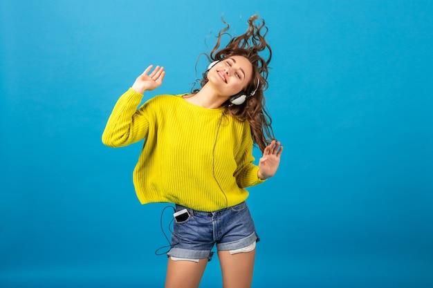 Привлекательная улыбающаяся счастливая женщина танцует, слушая музыку в наушниках в стильном хипстерском наряде, изолированном на синем фоне студии, в шортах и желтом свитере Бесплатные Фотографии