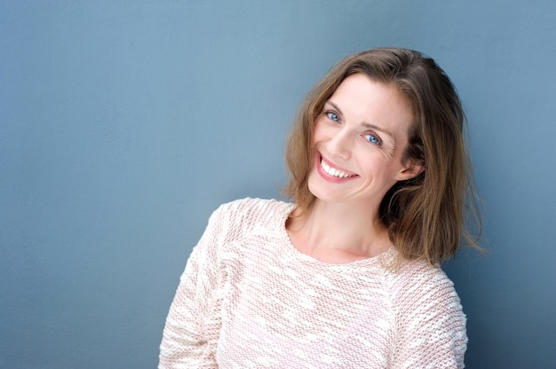 Attractive smiling mid adult woman on blue background Premium Photo