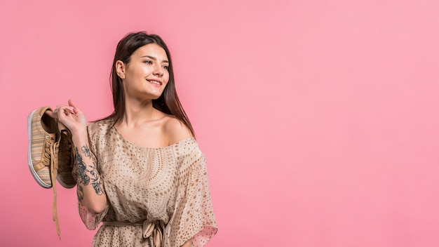 Attractive smiling woman holding shoes Free Photo