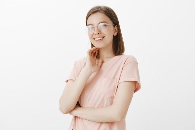 Привлекательная улыбающаяся женщина в очках, выглядящая мечтательно Бесплатные Фотографии
