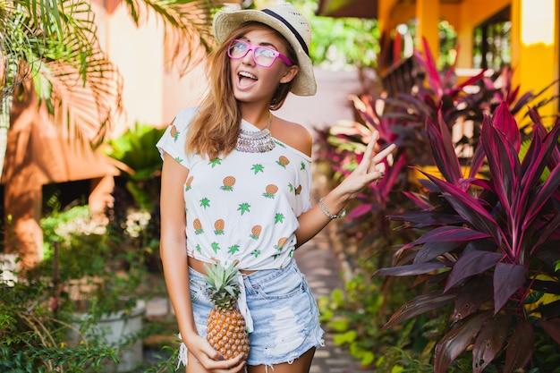 印刷されたtシャツ麦わら帽子夏のファッション、パイナップルを持って手で休暇中の魅力的な笑顔 無料写真