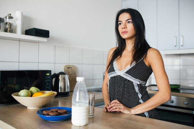 Attraente donna sorridente in pigiama facendo colazione in cucina la mattina, a tavola con biscotti e latte, stile di vita sano Foto Gratuite