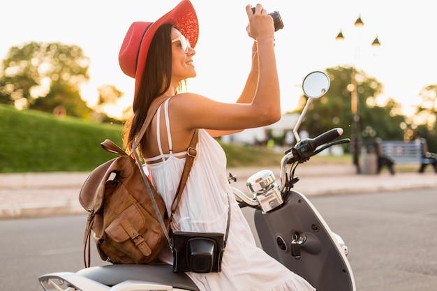 Привлекательная улыбающаяся женщина, едущая на мотоцикле по улице в летнем стиле, в белом платье и красной шляпе, путешествующая с рюкзаком в отпуске, фотографируя на старинную фотокамеру Бесплатные Фотографии