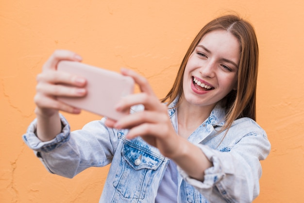 Attractive smiling woman taking selfie against beige wall Free Photo