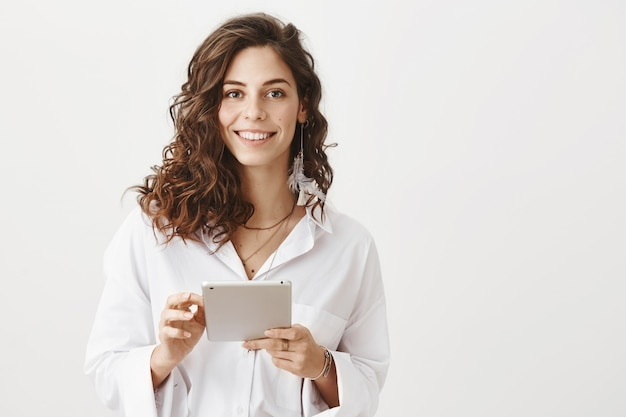 Attractive smiling woman using digital tablet Free Photo