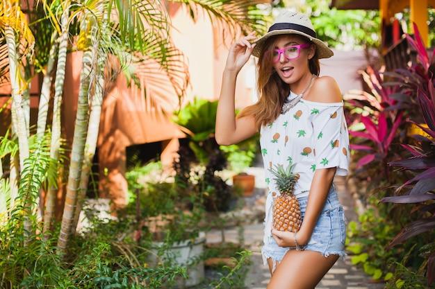 Attraente donna sorridente in vacanza in t-shirt stampata moda estate cappello di paglia, mani che tengono ananas Foto Gratuite