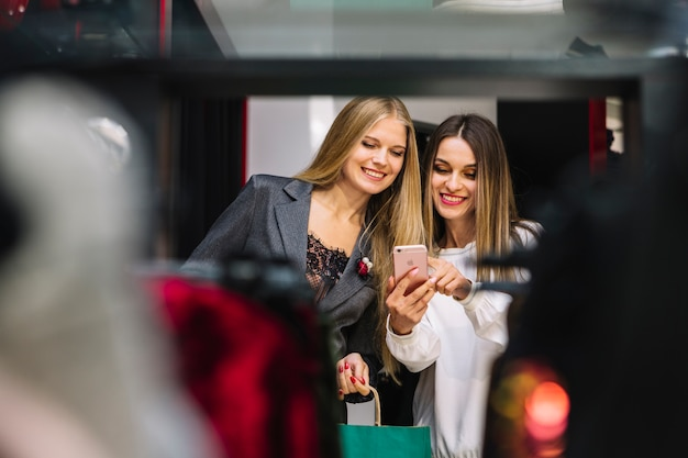 An attractive smiling young women looking at mobile phone Free Photo