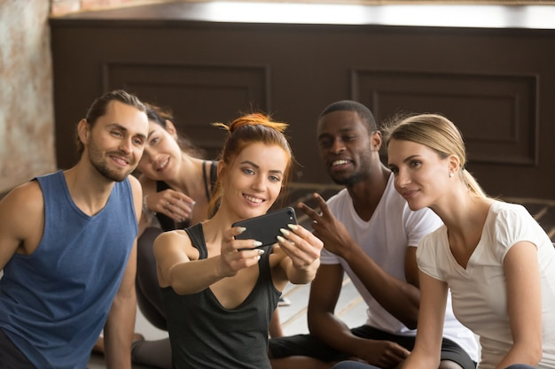 Attractive sporty woman holding phone taking group selfie at tra Free Photo