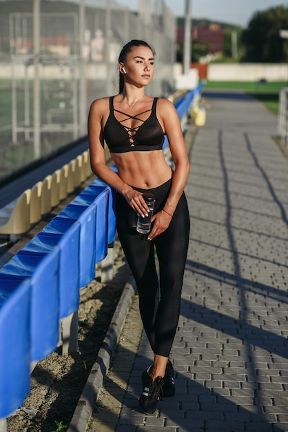 Attractive sporty woman with wireless headphones and bottle of water listening to music while training on an outdoors sports ground. Premium Photo