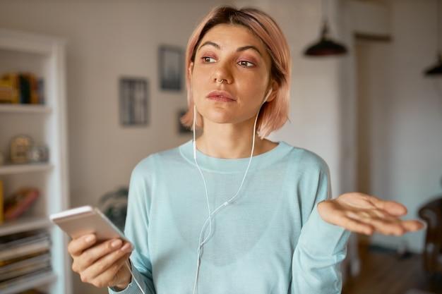 スマートフォンのビデオチャットを介して友人とオンラインで通信し、計画について話し合い、身振りで示す間、イヤフォンとマイクセットを使用する魅力的な学生の女の子。 無料写真