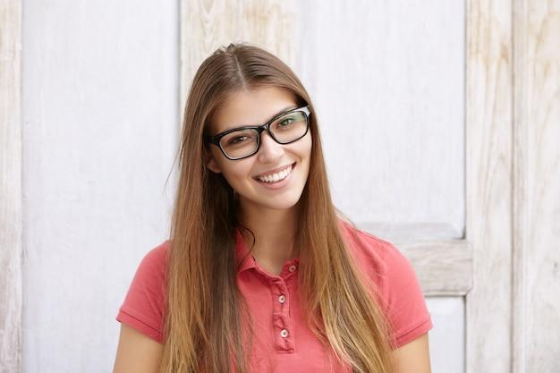 Привлекательная девушка студент с очаровательной улыбкой позирует Бесплатные Фотографии