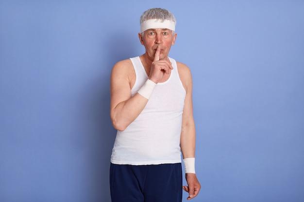 白いノースリーブのtシャツを着て、静かなジェスチャーをし、唇に前指を持ち、秘密を守るように頼み、ポーズをとる魅力的なスタイリッシュな年配の男性。 無料写真