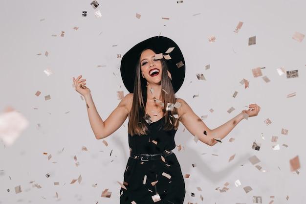 Modello femminile alla moda attraente in costume della strega che prepara per la festa di halloween sulla parete isolata con i coriandoli che ballano, divertendosi, sorridente. compleanno, vacanza Foto Gratuite
