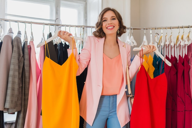 Attractive stylish smiling woman choosing apparel in clothing store Free Photo
