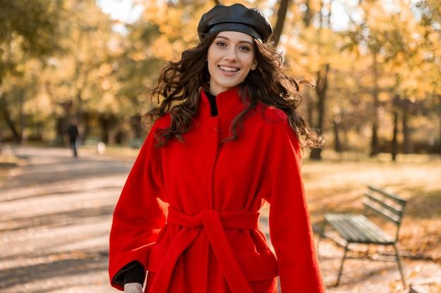 暖かい赤いコート秋の流行のファッション、ストリートスタイル、ベレー帽の帽子をかぶって公園を歩く巻き毛の魅力的なスタイリッシュな笑顔の女性 無料写真