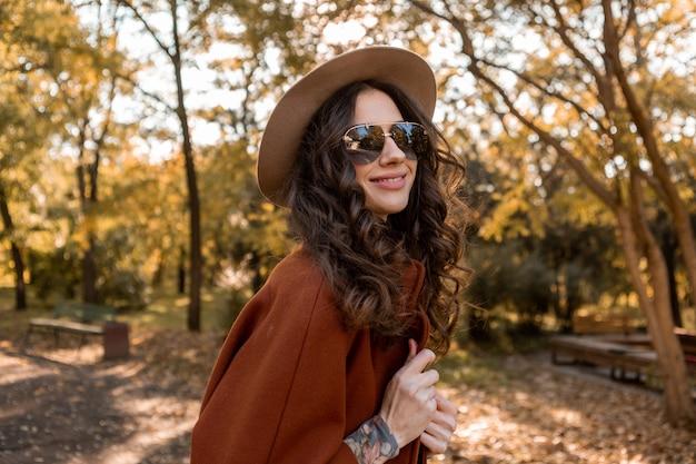 Привлекательная стильная улыбающаяся женщина с вьющимися волосами гуляет в уличном парке, одетая в теплое коричневое пальто осенней модной моды, уличного стиля в шляпе и солнцезащитных очках Бесплатные Фотографии
