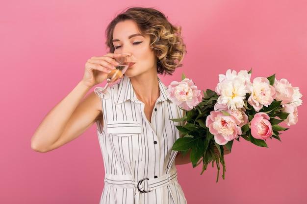 Attraente donna elegante alla data in elegante abito a righe bianche su sfondo rosa studio bevendo champagne in vetro, celebrando, tenendo il bouquet di fiori di peonia, bellissimo stile moda, alcol Foto Gratuite
