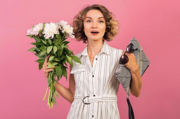 핑크 스튜디오 배경 감정적 인 얼굴 표현, 놀란, 핸드백, 꽃다발, 재미, 곱슬 헤어 스타일, 패션 여름 트렌드 액세서리에 우아한 흰색 줄무늬 드레스에 매력적인 세련된 여자 무료 사진