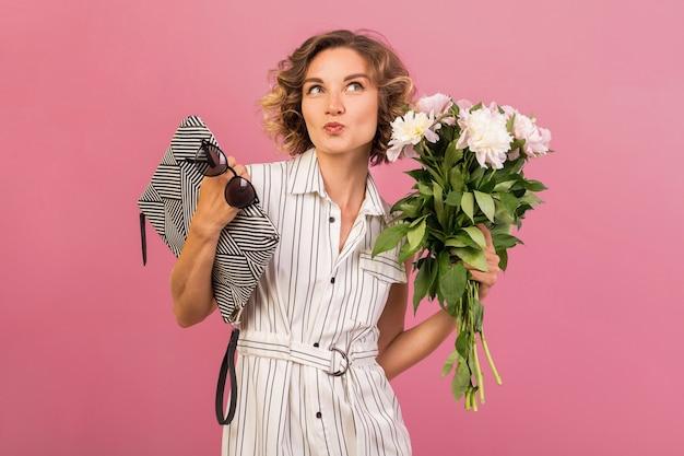 Привлекательная стильная женщина в элегантном белом полосатом платье на розовом студийном фоне эмоциональное выражение лица, удивленное, сумочка, букет цветов, забавная, вьющаяся прическа, модный летний аксессуар Бесплатные Фотографии