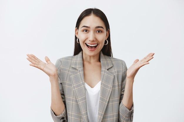 Attraente donna elegante in giacca e orecchini rotondi, gesticolando con le palme e sorridente Foto Gratuite