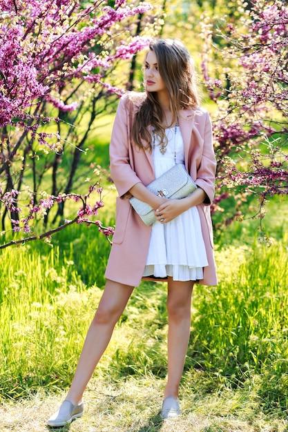明るい白いドレス、ピンクのコート、咲く桜と庭を歩く長い髪の魅力的なスタイリッシュな若い女性 無料写真