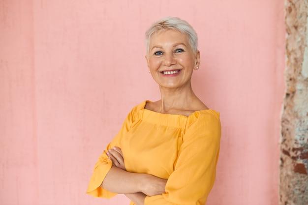 Привлекательная успешная блондинка-бизнесвумен средних лет с короткими волосами пикси и очаровательной уверенной улыбкой позирует изолированно на фоне пустой розовой стены, скрестив руки на груди Бесплатные Фотографии