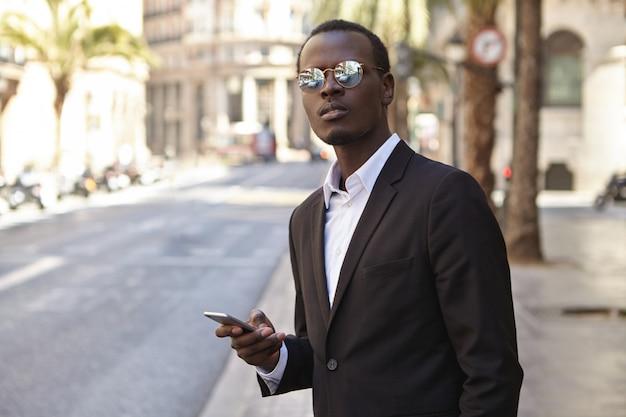 魅力的な成功した若いアフリカ系アメリカ人の起業家は、黒いフォーマルスーツとミラーレンズサングラスを身に着けて、スマートフォンが付いている通りに立って、タクシーを呼び起こし、焦りを待ち望んでいます。 無料写真