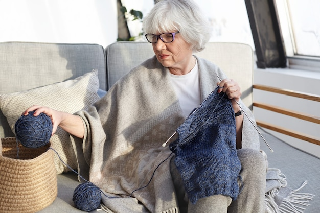 Attractive talented caucasian grandmother in eyeglasses enjoying her hobby sitting comfortably on sofa, holding yarn ball and kneedles, knitting sweater for her husband. people, age and leisure Free Photo