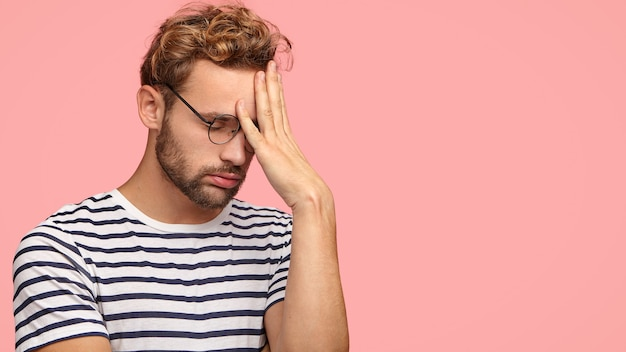 Imprenditore attraente uomo stanco oberato di lavoro sospira di stanchezza, tiene la mano sulla fronte, soffre di mal di testa Foto Gratuite