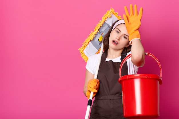 Attractive tired young female keeps hand on forehead, puts mop on shoulder. Premium Photo