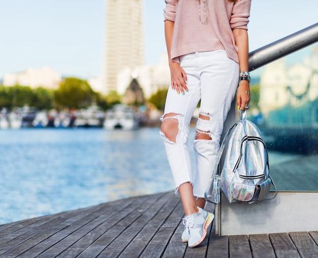 Привлекательная туристическая белокурая женщина, позирующая наружный в солнечный день, ветренную погоду. яркий макияж. носить розовый пастельный свитер и неоновый рюкзак. подробности. Бесплатные Фотографии